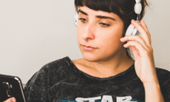 woman with black bangs listening to headphones and looking at phone