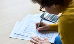 a person with a yellow sweater and curly black hair works on tax forms