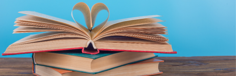 a stack of books against a blue background, the pages are folded into a heart