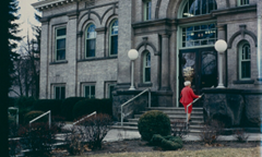 a person in a red skirt suit walks up the stone steps of the historic Boise Public Library Carnegie building