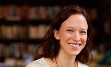 Photo of smiling young woman, linking to Ask A Librarian information and form